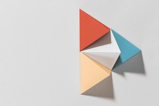 3d buntes pyramidenpapierhandwerk auf grauem hintergrund