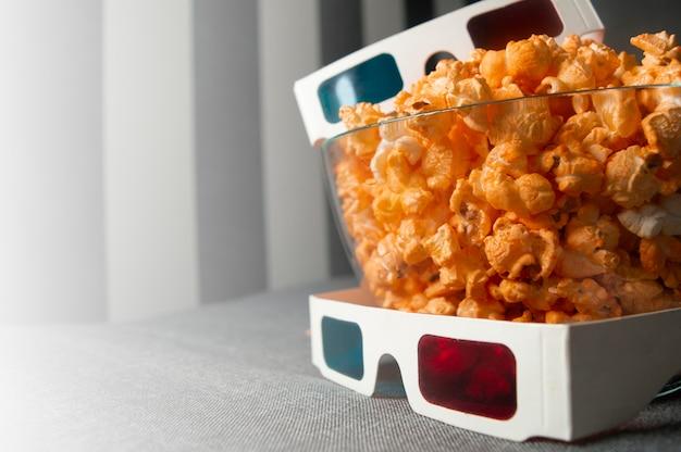 3d-gläser und käsiges popcorn liegen in einer glasplatte auf einem grauen bett