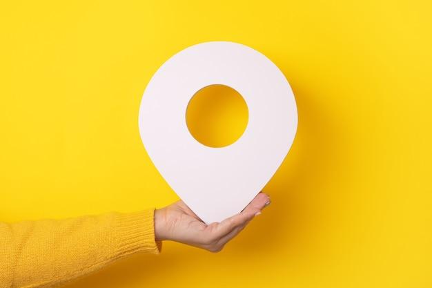 3d-ortssymbol in der hand über gelbem hintergrund