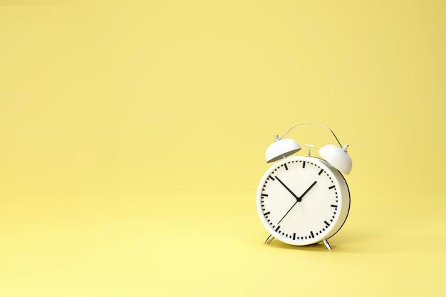 3d-rendering . weißer vintage-wecker mit einem leuchtend gelben hintergrund. minimales kreatives ideenkonzept.