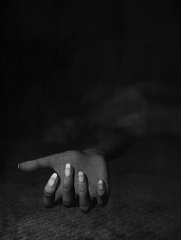 3d übertragen von einem dunklen grunge bild einer frau auf dem boden liegend mit ihrem ausgestreckten arm verlegung