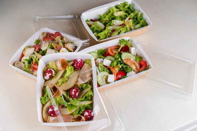 4 grüne natursalate in öko-thermobox mit microgreen, kalb, gurke, tomate, käse, granat, schale. sicherheitslieferung bei quarantäne covid 19.