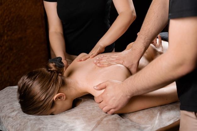 4-hand-massage im spa. zwei masseure machen vier hände entspannende massage mit öl für mädchen. entspannung. manuelle therapie.