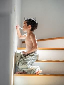 4 jahre altes asiatisches kind zu hause. zeichnen oder malen sie die wand zu hause.