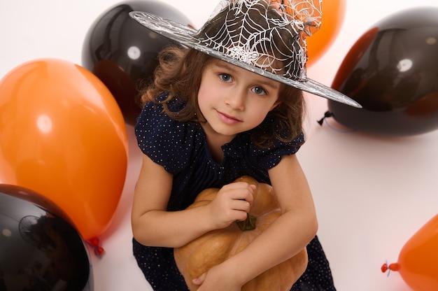 4 jahre altes entzückendes hübsches kleines mädchen in hexenkleid und zauberhut schaut in die kamera, die mit luftballons und einem kürbis auf weißem hintergrund spielt. konzept eines kindes, das spaß auf der halloween-party hat