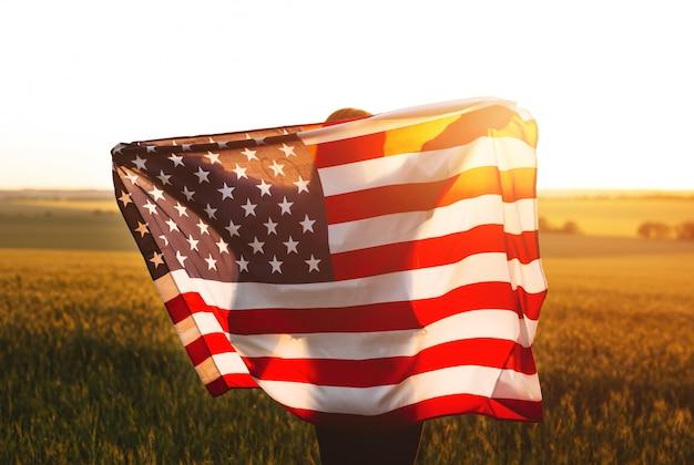 4. juli. frau mit der amerikanischen flagge, die in einem weizenfeld bei sonnenuntergang läuft. unabhängigkeitstag, patriotischer feiertag.