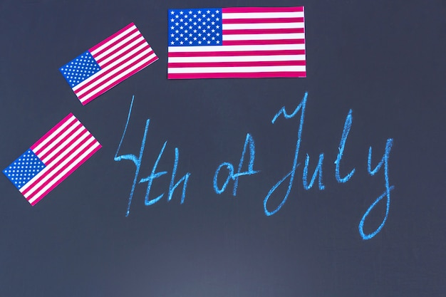 4. juli hintergrund mit schriftzug auf schwarzer kreidetafel und usa-flaggen