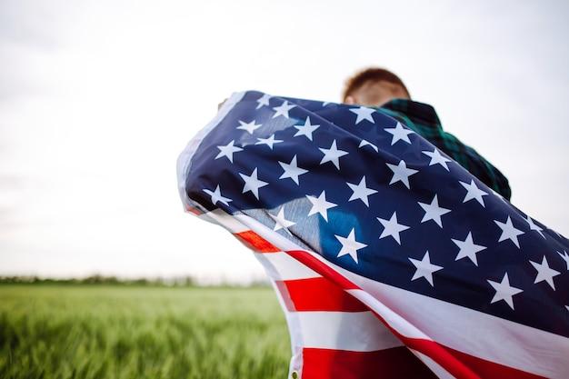 4. juli. tag der unabhängigkeit. ein mann mit der amerikanischen flagge in den händen auf einem grünen weizenfeld.