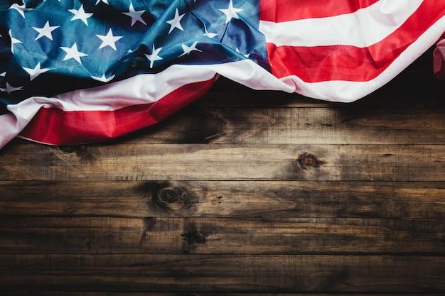 4. juli, us-unabhängigkeitstagbild mit us-flagge auf hölzernem hintergrund. von oben betrachten. flacher boden. speicherplatz kopieren.