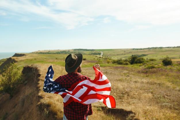 4. juli. vierter juli. amerikaner mit der nationalflagge. amerikanische flagge. tag der unabhängigkeit. patriotischer urlaub. der mann trägt einen hut, einen rucksack, ein hemd und jeans.