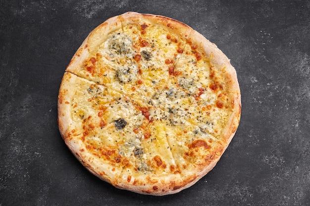 4 käsepizza auf einem dunklen tisch