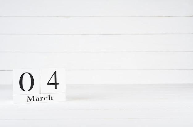 4. märz, tag 4 des monats, geburtstag, jahrestag, holzblockkalender auf weißem hölzernem hintergrund mit kopienraum für text.