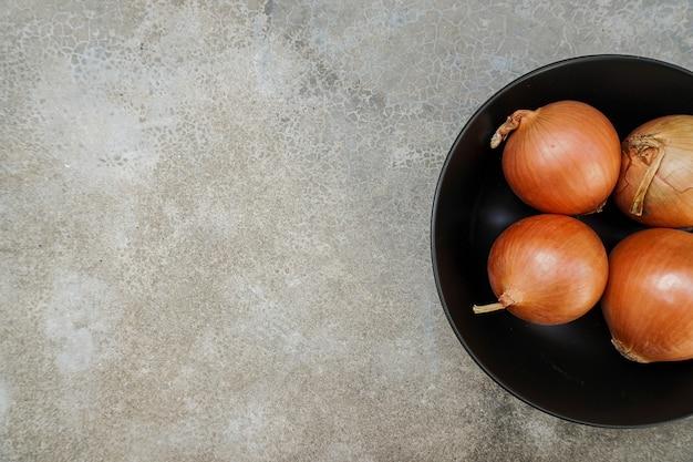 4 rohe zwiebeln mit schalen in einer schwarzen schale auf grauem hintergrund
