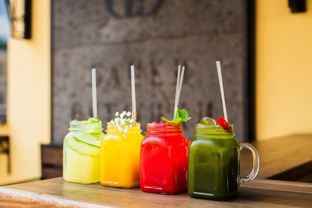 4 verschiedene erfrischende sommerlimonaden in gläsern, rot, orange, gelb und grün, draußen geschossen
