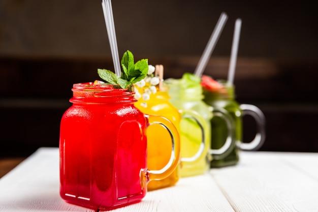 4 verschiedene erfrischende sommerlimonaden in gläsern