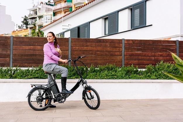 40-jährige frau fährt mit ihrem elektrofahrrad durch die straßen der stadt (konzept der elektromobilität)