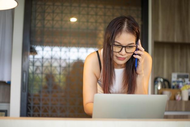 40 jahre alte frau benutzt zu hause telefon- und computerarbeit.