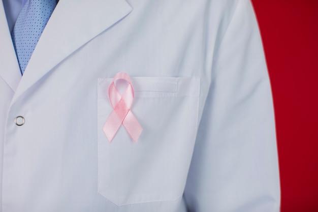 40er jahre arzt mit rosa band. krebsbewusstseinskonzept auf rot