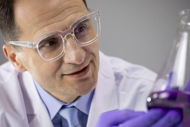 40er jahre männlicher arzt chemikerforscher lächelt und prüft die violette flüssigkeit im kolben