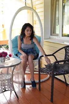 45 jahre alte russin ruht auf hängendem schaukelstuhl auf gemütlicher veranda mit schlafender katze