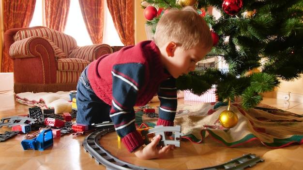 4k-aufnahmen des kleinen jungen erhielten spielzeugeisenbahn und zug zu weihnachten vom weihnachtsmann. kind baut schienen um weihnachtsbaum im wohnzimmer