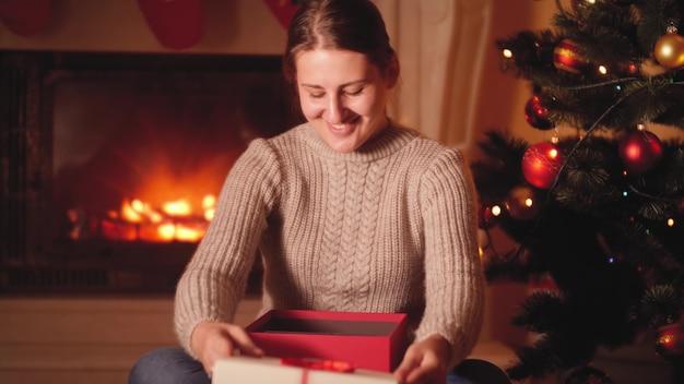 4k-aufnahmen einer lächelnden jungen frau, die ein digitales tablet als weihnachtsgeschenk vom weihnachtsmann erhalten hat