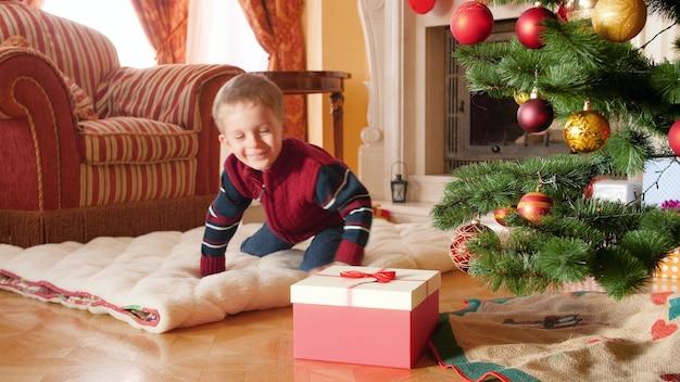 4k-aufnahmen eines glücklich lächelnden kleinen jungen öffnen sein weihnachtsgeschenk vom weihnachtsmann und nehmen eine spielzeugeisenbahn heraus. kinder, die an winterferien und an feiertagen geschenke und geschenke erhalten
