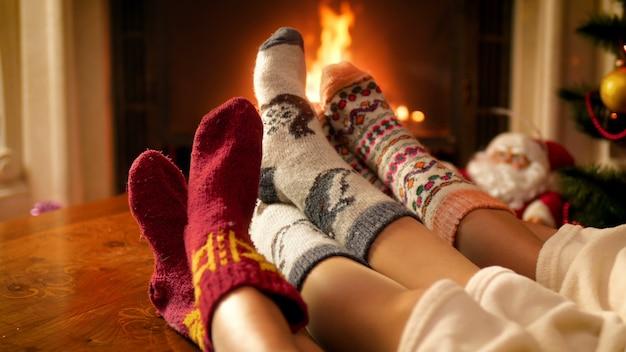 4k-aufnahmen von eltern mit kindern, die warme wollsocken tragen, die unter einer decke liegen und sich am brennenden kamin im wohnzimmer wärmen. menschen entspannen im winterurlaub und feiern zu hause