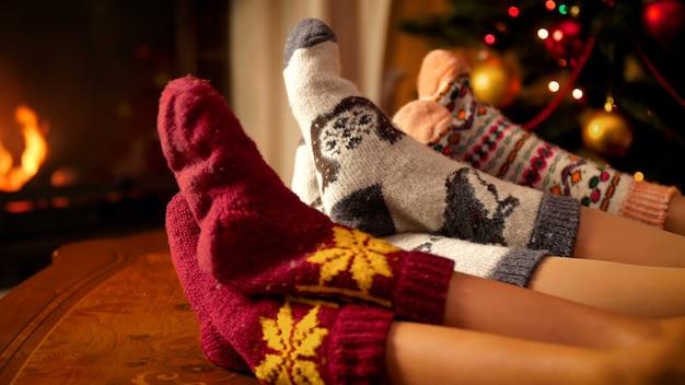 4k-aufnahmen von familien, die wollsocken tragen, die sich am feuer im kamin im wohnzimmer wärmen, das zum feiern von weihnachten oder neujahr dekoriert ist. menschen entspannen im winterurlaub und feiern zu hause