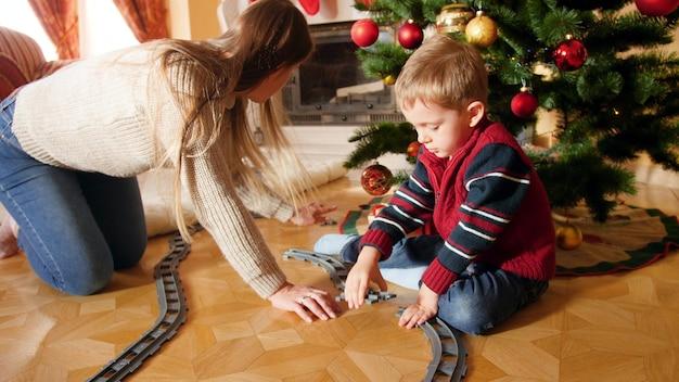 4k-aufnahmen von glücklich lächelnder mutter, die ihrem sohn beim bau einer eisenbahnstrecke aus ziegeln unter dem christams-baum hilft. kind erhält geschenke und geschenke vom weihnachtsmann an winterferien und an feiertagen