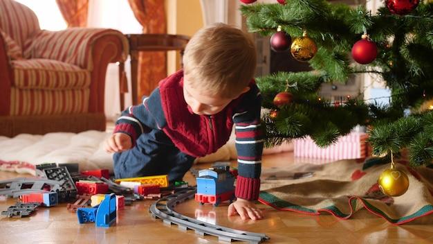 4k-aufnahmen von kleinen jungen, die eine spielzeugeisenbahn um den weihnachtsbaum im wohnzimmer bauen. kinder, die an winterferien und an feiertagen geschenke und geschenke erhalten