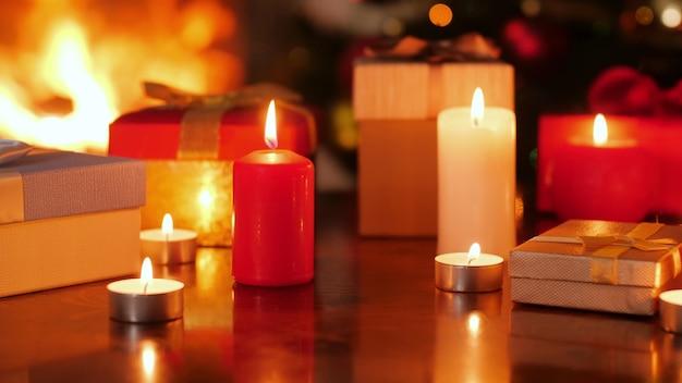 4k-dolly-aufnahmen von brennenden kerzen und kisten mit weihnachtsgeschenken im wohnzimmer mit kamin und weihnachtsbaum