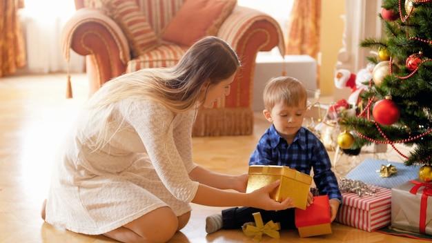 4k-filmmaterial einer glücklichen jungen mutter, die mit ihrem kleinen sohn unter dem weihnachtsbaum sitzt und weihnachtsgeschenke und -geschenke öffnet. familie, die an winterferien und -feiern geschenke gibt und empfängt.