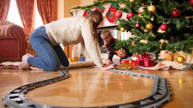 4k-filmmaterial einer glücklichen, lächelnden familie mit einem kleinen jungen, der eine eisenbahn für eine kleine spielzeugeisenbahn um den weihnachtsbaum baut. kind erhält geschenke und geschenke vom weihnachtsmann an winterferien und an feiertagen