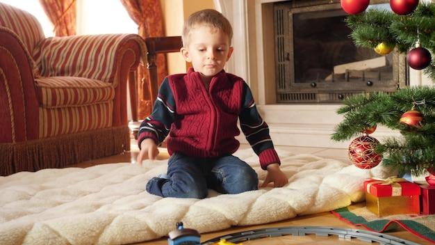 4k-filmmaterial eines kleinen kleinkindjungen, der die spielzeugeisenbahnfahrt auf der kreiseisenbahn im wohnzimmer betrachtet. kind erhält geschenke und geschenke vom weihnachtsmann an winterferien und an feiertagen