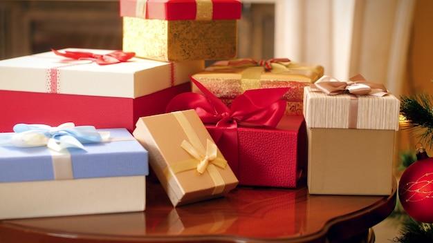 4k-schwenkaufnahmen von vielen weihnachtsgeschenken und geschenken vom weihnachtsmann auf holztisch und bunt geschmücktem weihnachtsbaum im wohnzimmer