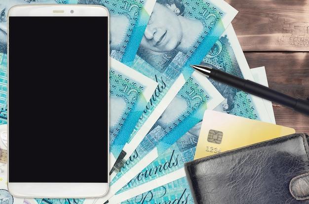 5 britische pfund rechnungen und smartphone mit geldbörse und kreditkarte