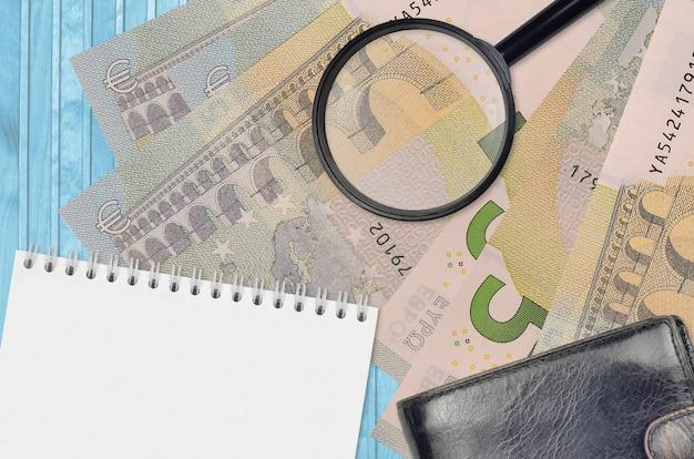 5 euro-scheine und lupe mit schwarzer geldbörse und notizblock