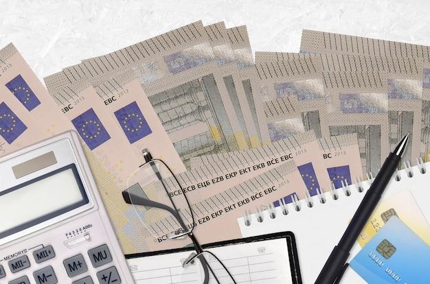 5 euro-scheine und taschenrechner mit brille und stift