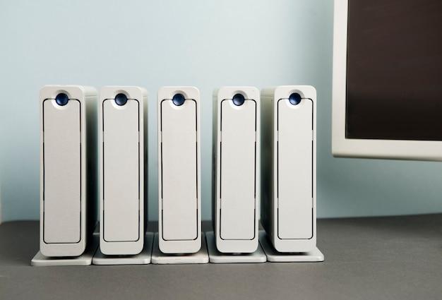 5 große aluminium-festplatten aufgereiht auf schwarzem tisch teilansicht silberner monitor grau-blauer wandhintergrund