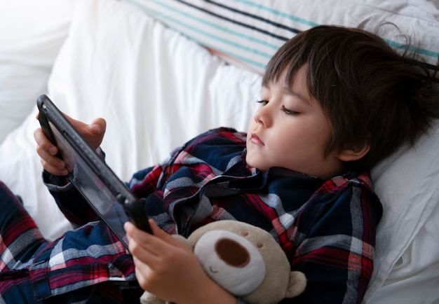 5 jahre alter junge, der morgens im bett spielt auf tablette im schlafzimmer liegt