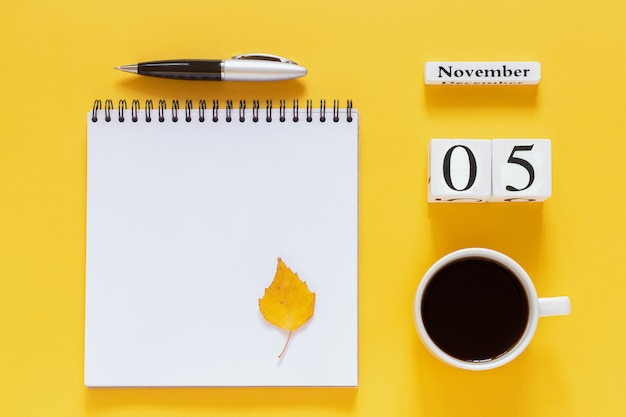5. november tasse kaffee, notizblock mit stift und gelbes blatt auf gelb