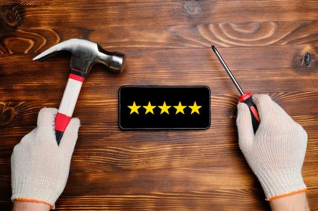 5-sterne-bewertung und bewertungskonzept - ein handschuh hält einen hammer und einen schraubenzieher in der nähe des smartphones an einer holzwand. draufsicht