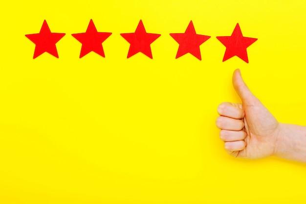 5 sterne erhöhen bewertung, customer experience konzept. hand des kunden zeigt 5-sterne-symbol, um die service-bewertung zu erhöhen. fünf rote sterne ausgezeichnete bewertung auf gelbem hintergrund. zufriedenheitskonzept