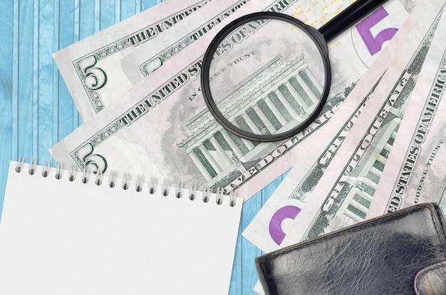 5 us-dollar-scheine und lupe mit schwarzer geldbörse und notizblock