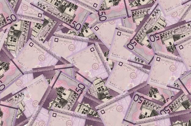 50 dominikanische pesos-scheine liegen auf einem großen haufen. reichhaltige konzeptionelle wand des lebens. großer geldbetrag