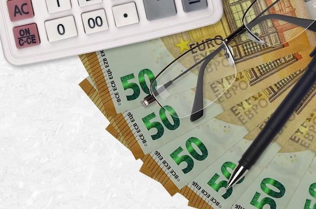 50 euro rechnungen fan und taschenrechner mit brille und stift. geschäftskredit- oder steuerzahlungssaisonkonzept