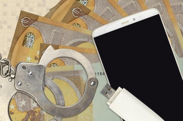 50 euro-scheine und smartphone mit polizeihandschellen