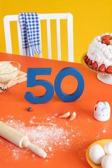 50. geburtstags-arrangement mit kuchenkochzutaten