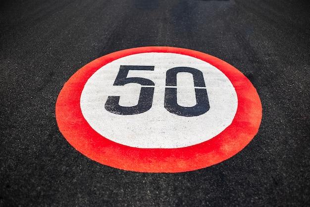 50 km / h geschwindigkeitsbegrenzungsschild auf dunkler asphaltstraße gemalt.